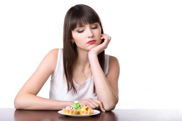 mulher olhando tristemente um prato com bolos 1163 1042 - Carboidrato engorda?